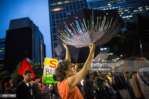 Demonstrator opens umbrellas upside down to catch rainwater during a protest against the lack of water that is affecting the entire state of Sao...