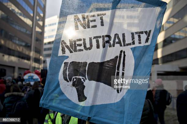 A demonstrator opposed to the roll back of net neutrality rules holds a sign outside the Federal Communications Commission headquarters ahead of a...