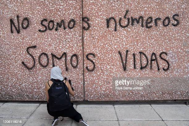 A demonstrator paints a graffiti that reads we are not numbers we are lives during a rally on International Women's Day on March 8 2020 in Mexico...