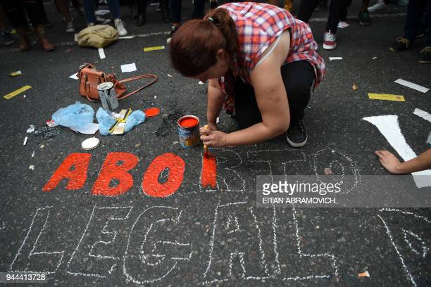 A demonstrator paints a legend on the street in demand of women's access to safe free and legal abortion during a rally outside the National Congress...