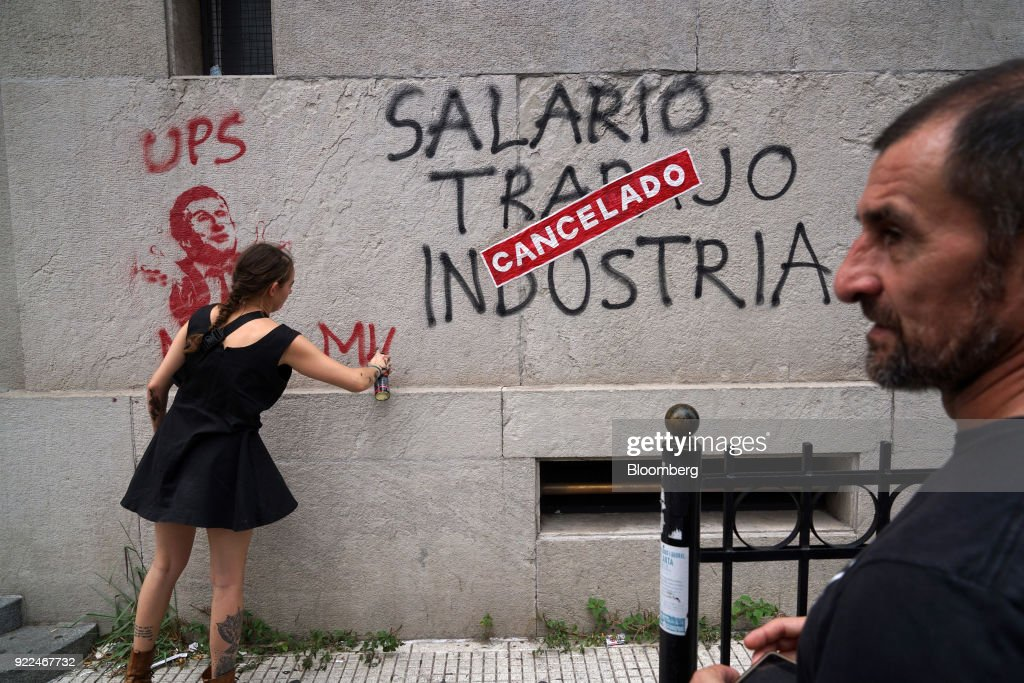 A demonstrator paints graffiti on a wall during a protest against President Mauricio Marci's economic policies in Buenos Aires, Argentina, on Wednesday, Feb. 21, 2018. Hugo Moyano, perhaps the most powerful union leader in the country, called the protest in a dispute over cuts to pension payments and dismissals as he heads for a showdown with Macri. The government claims it's a response to several allegations of corruption against Moyano. Photographer: Pablo E. Piovano/Bloomberg via Getty Images