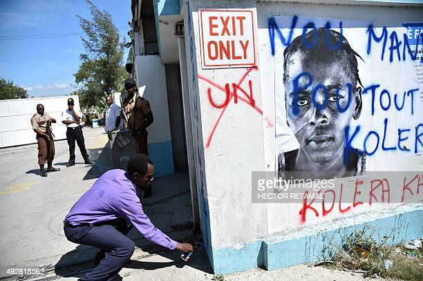 A demonstrator paints graffiti while Haitian human rights and victims of cholera rally in front of the Log Base of Minustah in PortauPrince on...