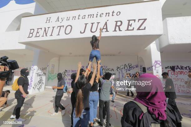 Demonstrator paints slogans on the facade of the Cancun Attorney General's Office during a protest called by feminist collectives against genre...