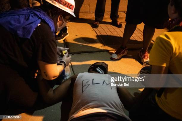 A demonstrator passes out during a clash with law enforcement on August 25 2020 in Kenosha Wisconsin As the city declared a state of emergency curfew...