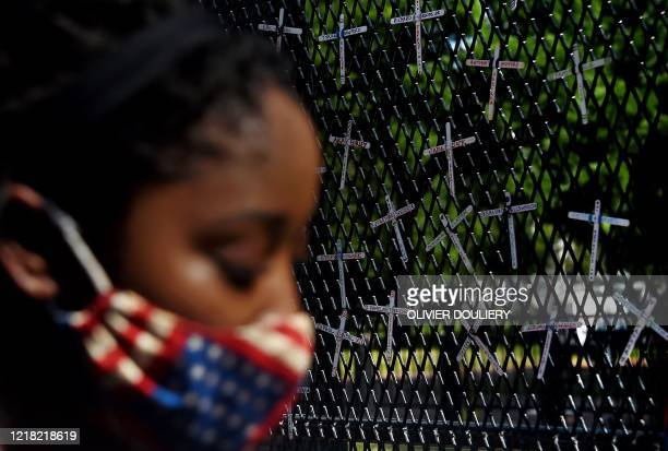 Demonstrator pauses in front of a wall displaying names of black people who have been killed by police, across from the White House during a peaceful...