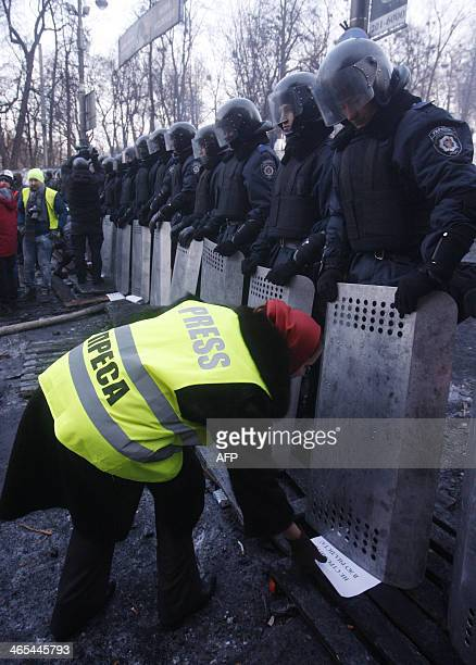 A demonstrator places signs in front of riot police as Ukrainian journalists protest against police violence in Kiev on January 27 2014 Ukraine on...