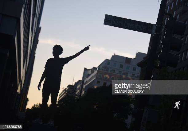 A demonstrator points to a sign at the newly renamed Black Lives Matter Plaza during a protest against police brutality and the death of George Floyd...