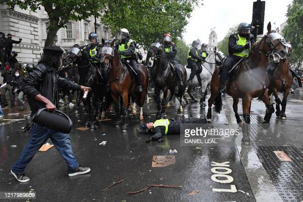 A demonstrator points towards a mounted police officer laying in the road after being unseated from their horse during a demonstration on Whitehall...