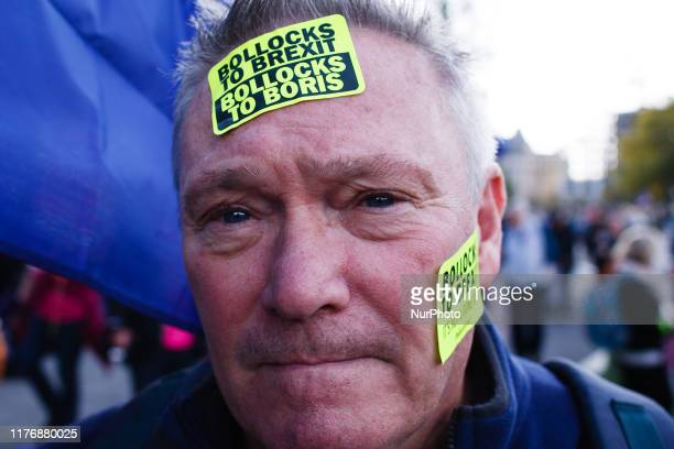 A demonstrator poses for a photo with 'Bollocks To Brexit Bollocks To Boris' stickers on his face as people gather on Park Lane for the mass...