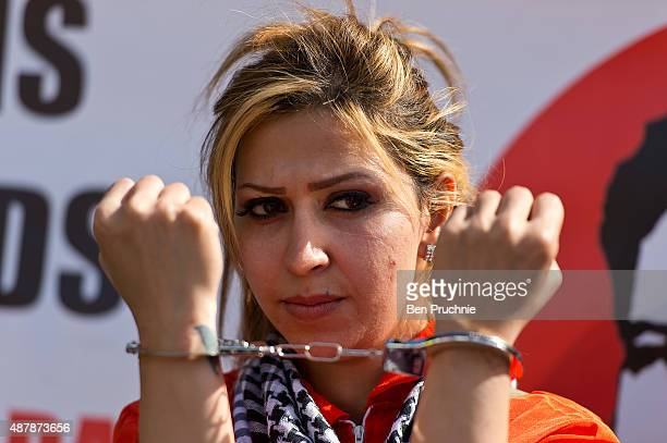 A demonstrator poses with handcuffs as she attends a march through Westminster on September 12 2015 in London England The demonstrators are calling...