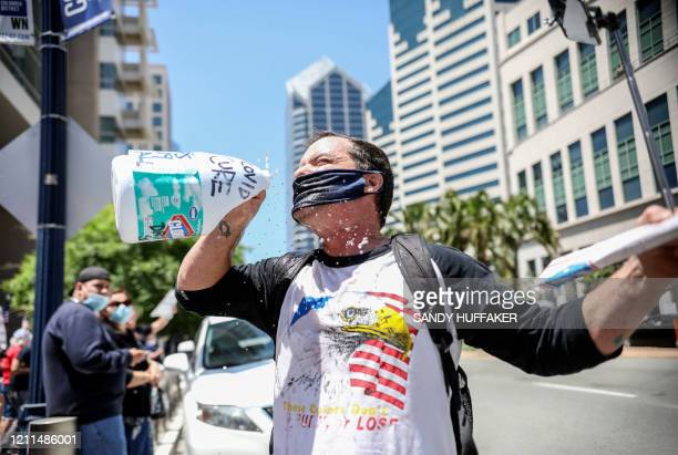 Demonstrator pours water on his mask as he pretends to drink from a bottle of bleach during a rally to re-open California and against Stay-At-Home...