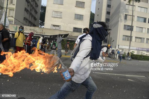 A demonstrator prepares to throw a Molotov cocktail at riot police during a march against Venezuelan President Nicolas Maduro in Caracas on April 19...