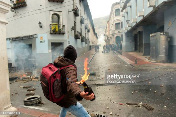 A demonstrator prepares to throw a Molotov cocktail at the police following the announcement of a transport strike against the economic policies of...