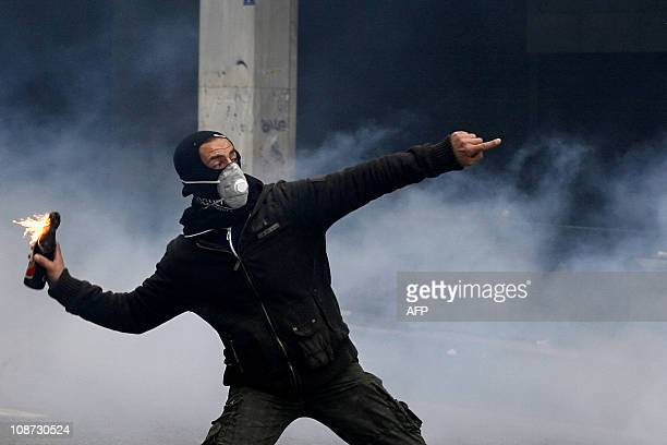 A demonstrator prepares to throw a petrol bomb during a protest in Athens on December 15 2010 against the socialist government's austerity policies...