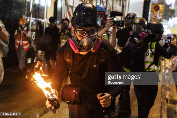 A demonstrator prepares to throw a petrol bomb towards riot police on Hennessy Road during a protest in the Causeway Bay district of Hong Kong China...