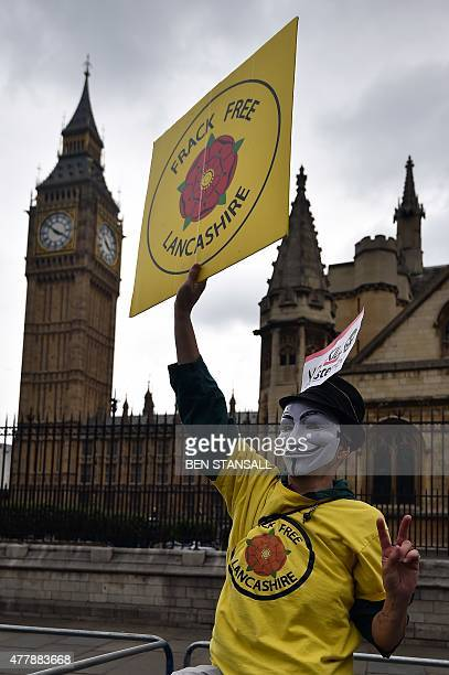 A demonstrator protesting against fracking in Lancashire holds a placard in front of the Houses of Parliament during a march against the British...