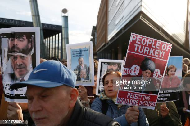 A demonstrator protesting against the policy of the Turkish President holds a poster reading Peopel of Turkey Reject this wouldbe dictator on the...