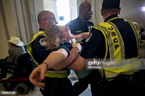 A demonstrator protesting cuts to Medicaid is carried away from the office of Senate Majority Leader Mitch McConnell by US Capitol police officers at...