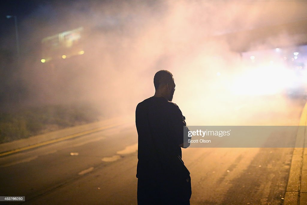 A demonstrator protesting the killing of teenager Michael Brown by a Ferguson police officer stands in a cloud of tear gas after the protest was attacked by police on August 17, 2014 in Ferguson, Missouri. Despite the Brown family's continued call for peaceful demonstrations, violent protests have erupted nearly every night in Ferguson since his death.