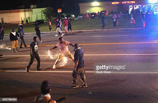 A demonstrator protesting the killing of teenager Michael Brown by a Ferguson police officer throws a tear gas grenade back toward police after the...