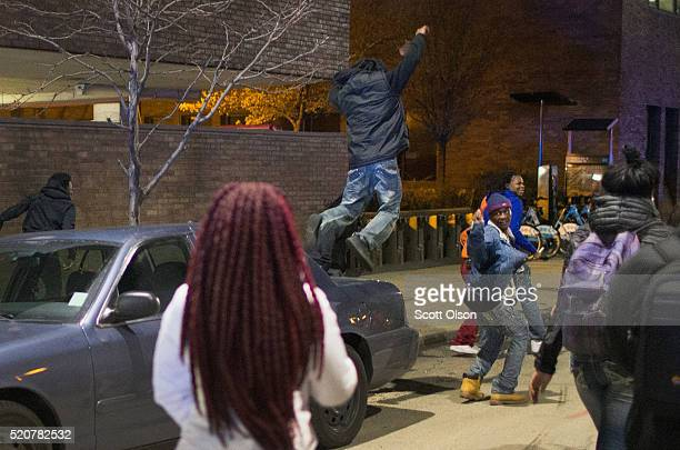 Demonstrator protesting the shooting death of 16-year-old Pierre Loury jumps off a police car during a march on April 12, 2016 in Chicago,...