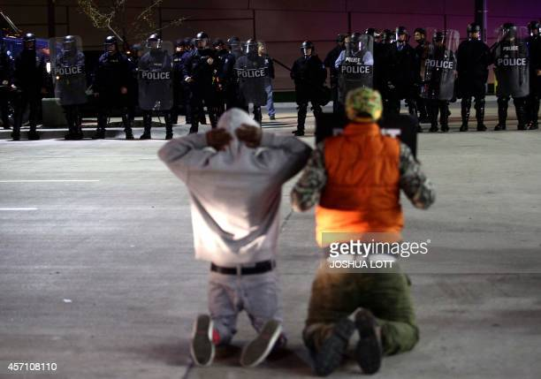 Demonstrator protesting the shooting death of Michael Brown and 18yearold Vonderrit Myers Jr kneel as they face police officers in riot gear in St...