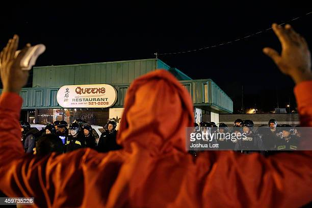 A demonstrator protesting the shooting death of Michael Brown confronts police officers with his hands up November 29 2014 in Ferguson Missouri Brown...