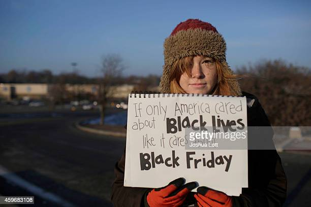 A demonstrator protesting the shooting death of Michael Brown holds a sign near the entrance to a local Walmart store on Black Friday November 28...