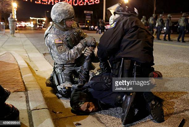 A demonstrator protesting the shooting death of Michael Brown is arrested by a National Guard troop and a police officer outside of the Ferguson...