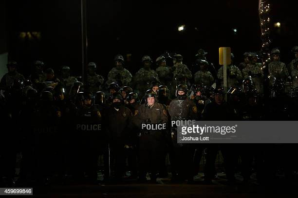 Demonstrator protesting the shooting death of Michael Brown shines a spot light on a group of police officers and National Guard troops outside of...