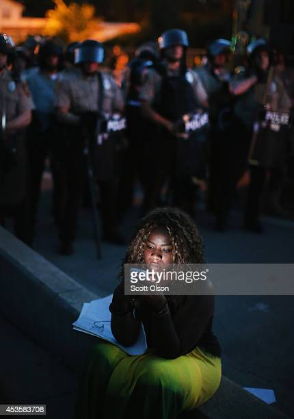 A demonstrator protesting the shooting death of teenager Michael Brown looks at her phone as police keep watch nearby on August 13 2014 in Ferguson...