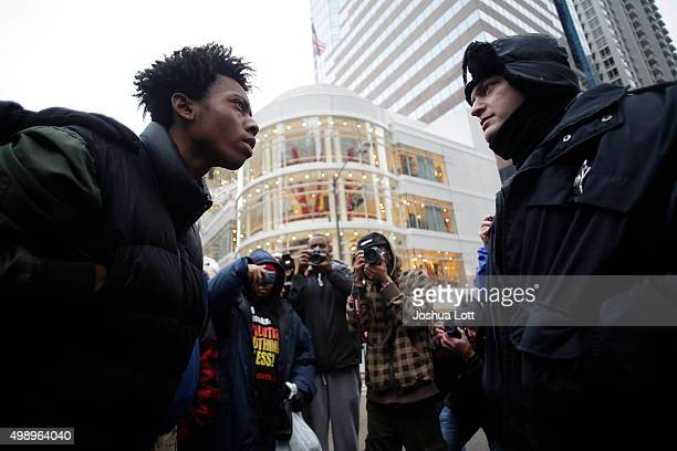 A demonstrator protesting the shooting of Laquan McDonald who was killed by a Chicago police Officer stares down a police Officer along the Michigan...