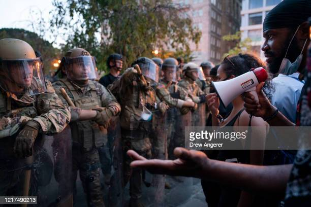 A demonstrator protests as police forces hold a line near Lafayette Park and the White House on June 3 2020 in Washington DC Protests in cities...