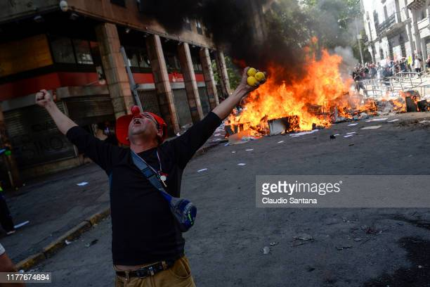 A demonstrator protests in front of a burning barricade during the fifth day of protests against President Sebastian Piñera on October 22 2019 in...