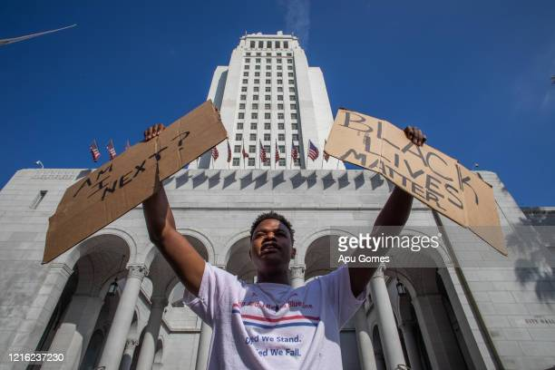 A demonstrator protests in front of Los Angeles City Hall in response to the police killing of George Floyd on May 29 2020 in Los Angeles California...