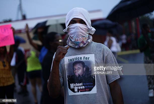 A demonstrator protests the shooting death of 18yearold Michael Brown on August 15 2014 in Ferguson Missouri Michael Brown was killed in broad...