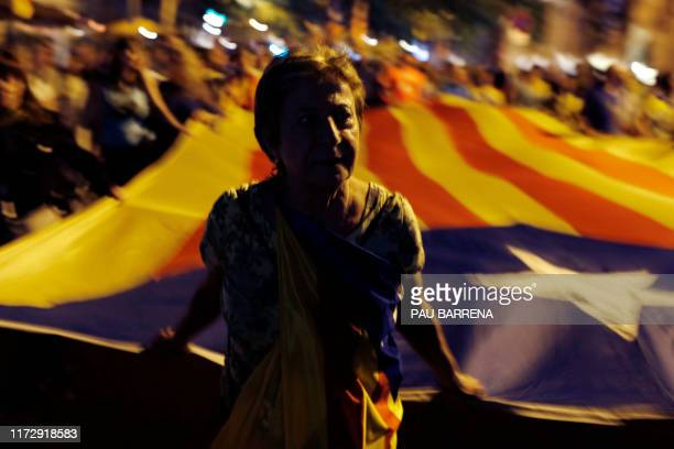 """Demonstrator pulls a giant Catalan pro-independence """"estelada"""" flag during a protest marking the 2nd anniversary of banned independence referenfum,..."""