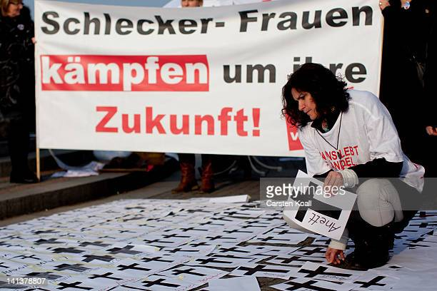 A demonstrator puts papers with black crosses on the ground as employees of Schlecker drug stores demonstrate against closure later this month on...
