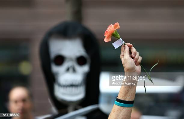 A demonstrator raises a flower during a protest in response to violence erupting at the rally in Charlottesville at Federal Plaza Square in Chicago...