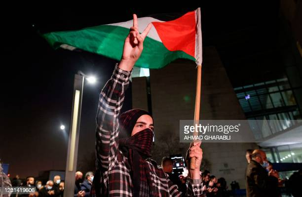 Demonstrator raises a hand with the victory gesture while holding a Palestinian flag outside the Haifa District Court in Israel's northern...