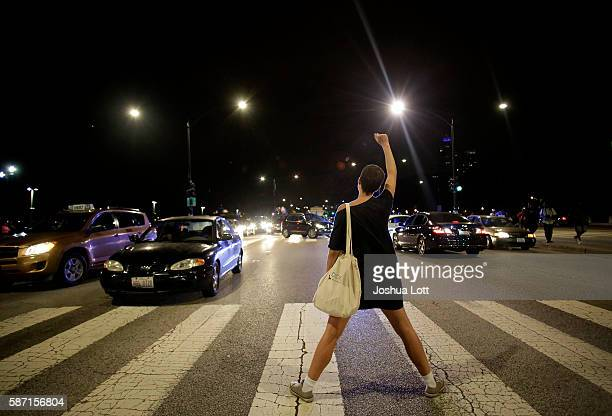 A demonstrator raises her fist as she blocks Lake Shore Drive during a protest for the fatal police shooting of Paul O'Neal August 7 2016 in Chicago...