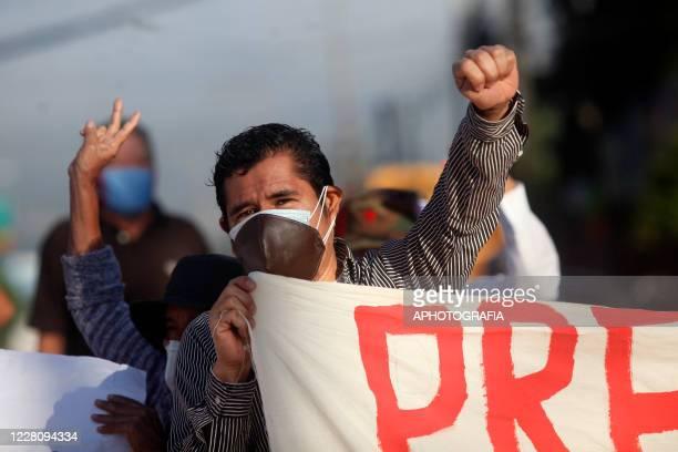 A demonstrator raises his fist and holds a banner during a veterans protest from the former guerrilla Frente Farabundo Marti Para La Liberacion...