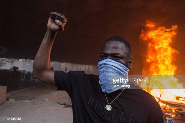 "Demonstrator raises his fist as he stands in front of burning pallets during a protest against police brutality near the ""Tribunal de Paris""..."
