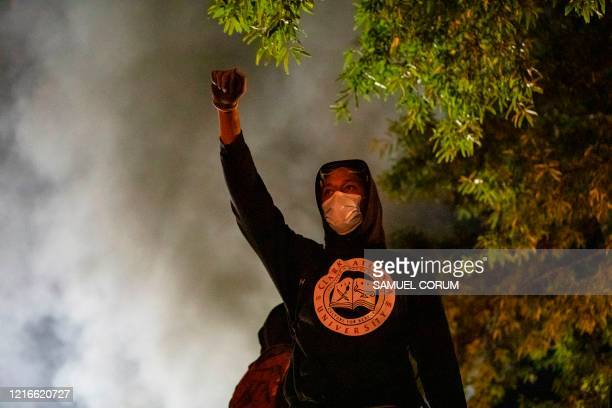 A demonstrator raises his fist during a face off with the police in front of the White House as he protests against the death of George Floyd at the...