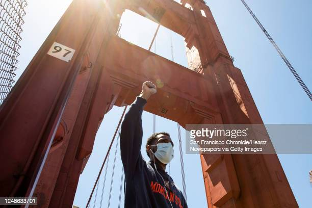 Demonstrator raises his fist in the air while sporting a mask as he makes his way with thousands of others across the Golden Gate Bridge in San...