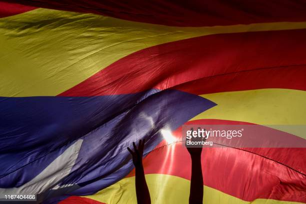 A demonstrator raises their arms while standing under a large proindependence Catalan Estelada flag during Catalonia's national day known as Diada...