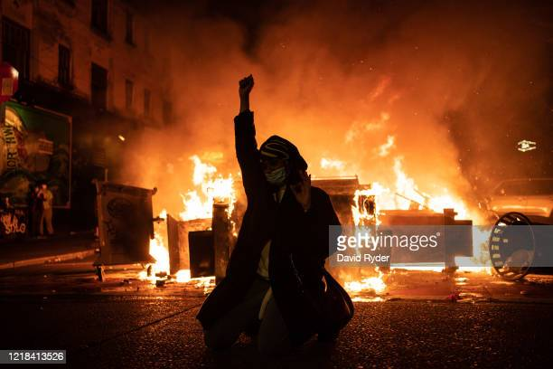 Demonstrator raises their fist as a fire burns in the street after clashes with law enforcement near the Seattle Police Departments East Precinct...