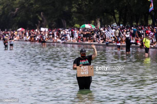 Demonstrator raises their fist in support of Black Lives Matter while standing in the Reflecting Pool during the Commitment March at the Lincoln...