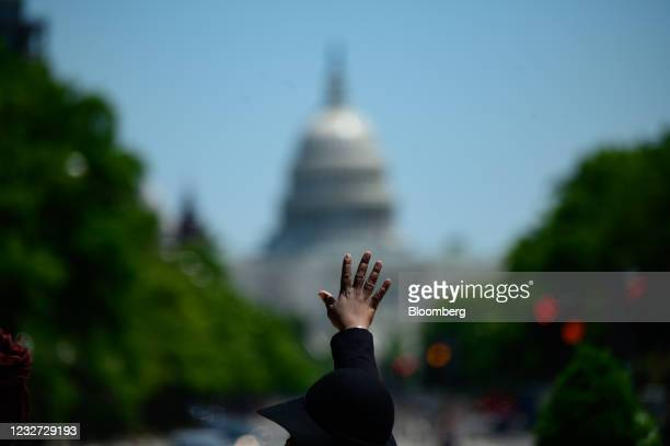 """Demonstrator raises their hand during a """"Hear the Cry"""" rally at Freedom Plaza near the U.S. Capitol in Washington, D.C., U.S., on Thursday, May 6,..."""