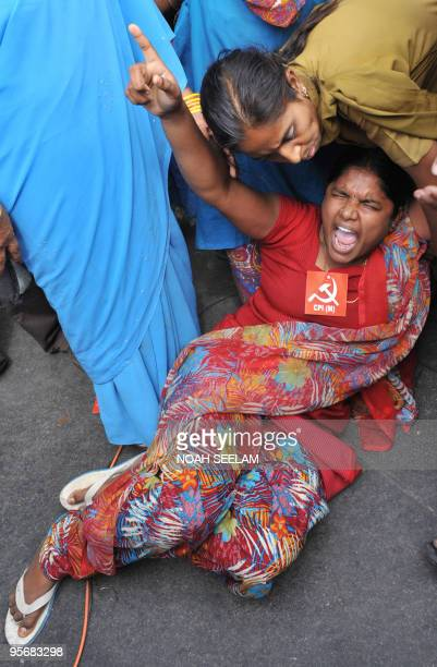 A demonstrator reacts as she blocks traffic during a protest organised by members of the Communist Party of India and Communist Party of...